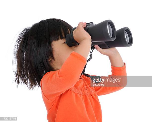 Little girl in orange shirt looking through black binoculars