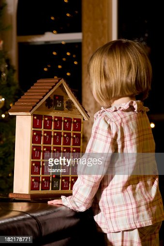 A little girl in pajamas playing with an advent calendar