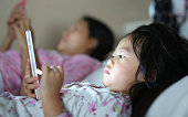Little girl in pajamas with mother playing smartphone lying on a bed.