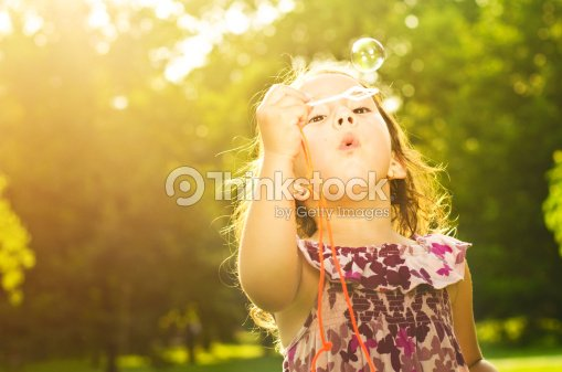 Little girl in park blowing bubbles : Stock Photo