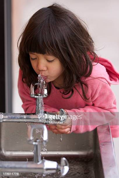 Little girl in pink sweater drinking from a water fountain