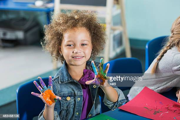 Little girl in preschool, hands covered with paint