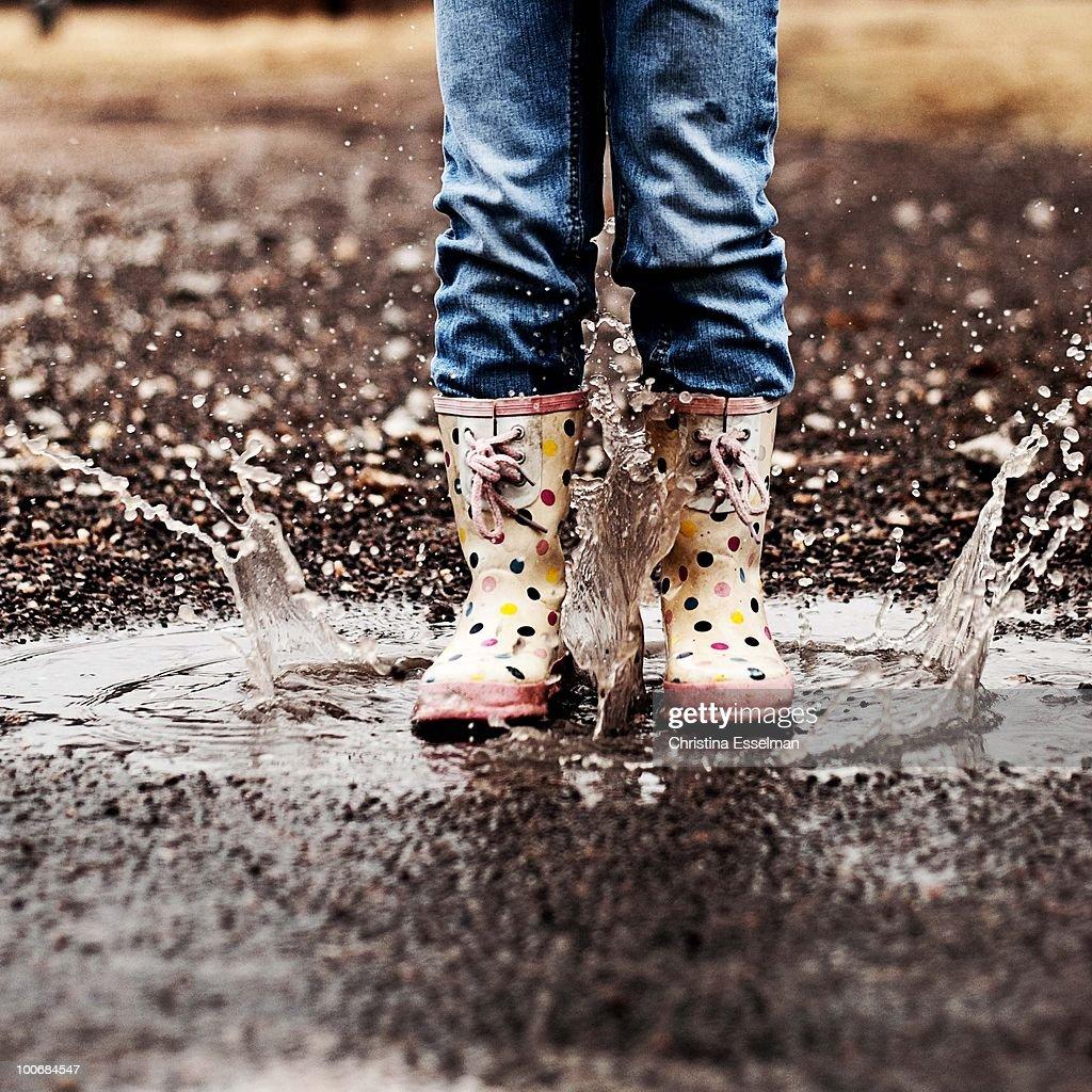 Little girl in rain boots, making a splash! : Stock Photo
