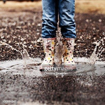 Little girl in rain boots, making a splash!