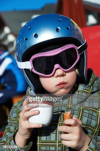 Little girl in ski helmet eats and  drinks : Stock Photo