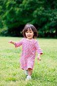 Little girl in stripy dress running across field