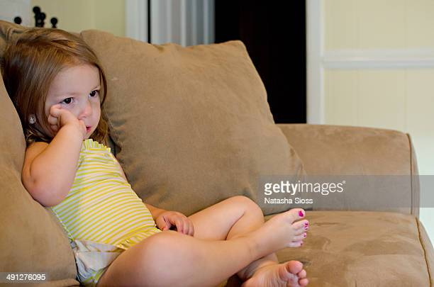 Little girl in swimsuit sitting on the couch