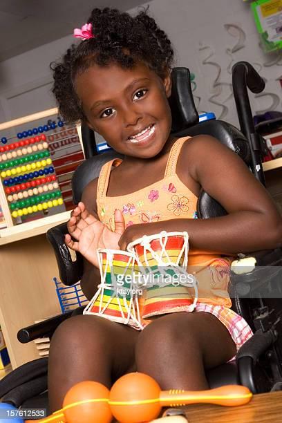 Bambina in una sedia a rotelle che giocano bongos a scuola