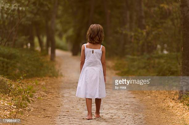Little girl in white dress in a forest