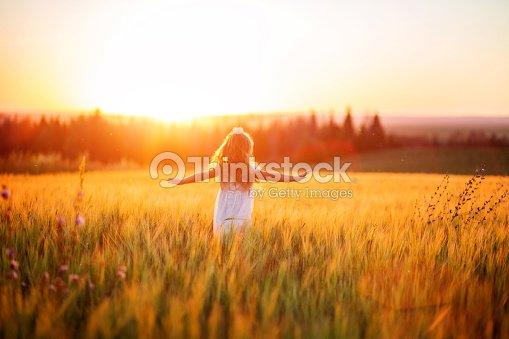 Little girl in white dress in field at sunset : Foto de stock