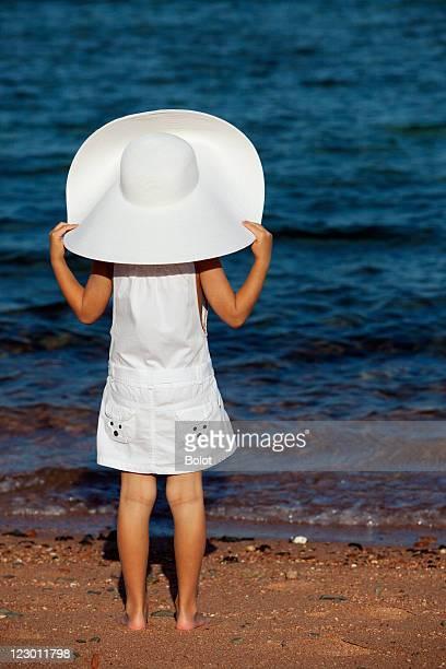 Little girl in white sun hat sitting on beach