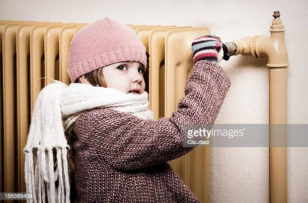 Little girl in winter cloth turns thermostat of old radiator