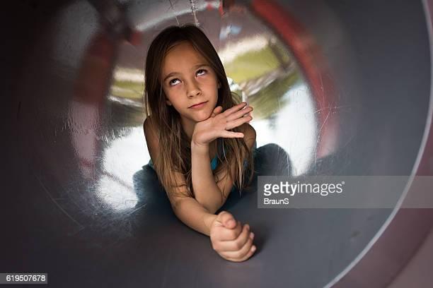Little girl inside of an outdoor play equipment.