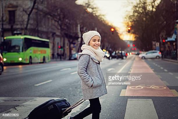 Little girl is crossing the street