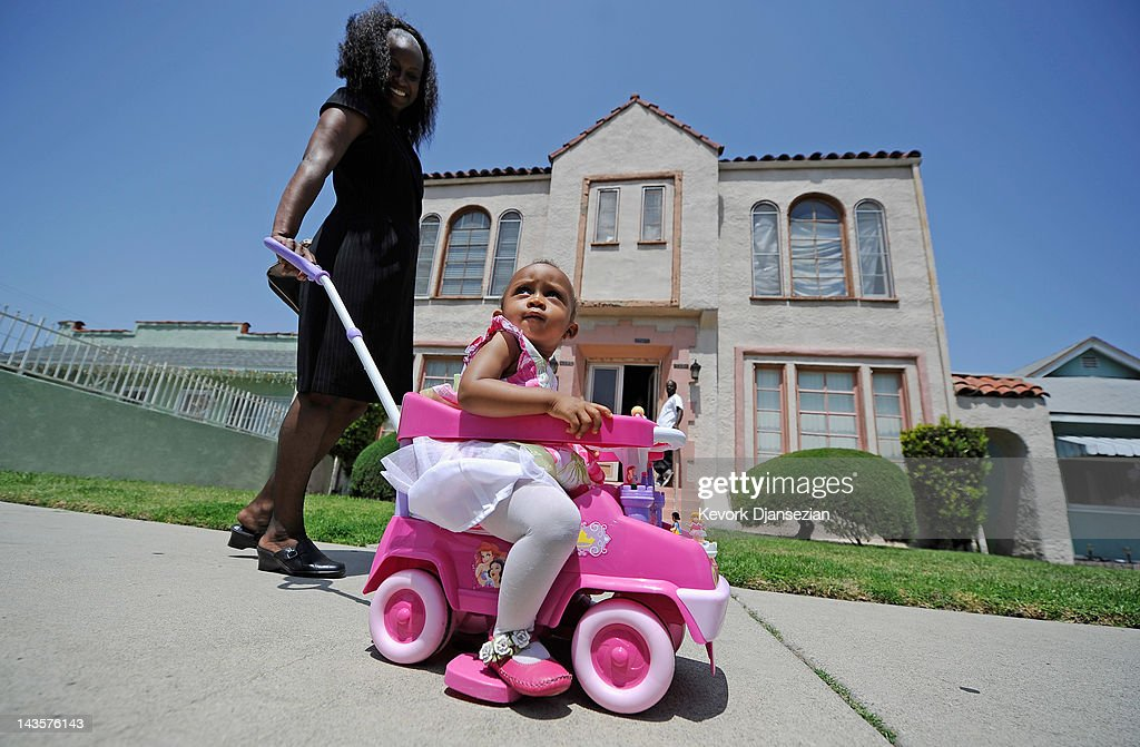 A little girl is escorted back home by her mother after a church service in South Los Angeles on April 29, 2012 in Los Angeles, California. It's been 20 years since the verdict was handed down in the Rodney King case that sparked the infamous Los Angeles riots.