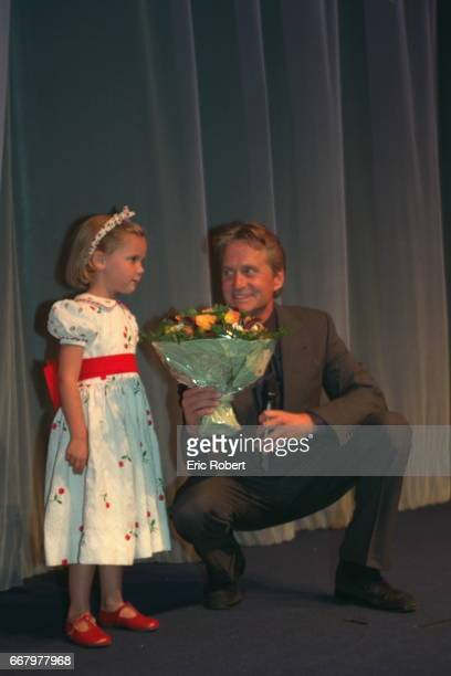 TRIBUTE TO MICHAEL DOUGLAS A little girl is handling a bunch of flowers to Michael Douglas