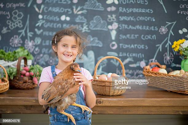 A little girl is holding her pet chicken and is standing
