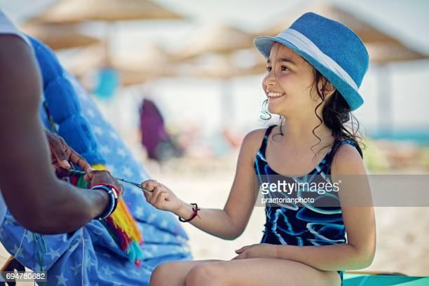 Little girl is knitting a bracelet on the beach
