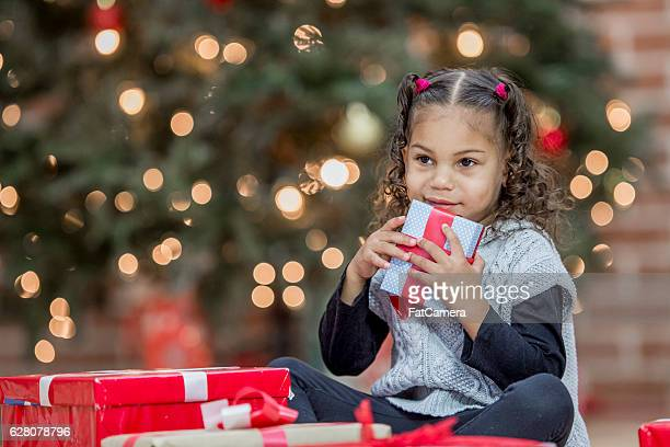 A little girl is opening presents on Christmas morning.
