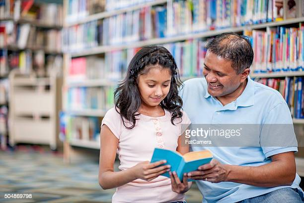 Little Girl is Reading a Book to Her Father