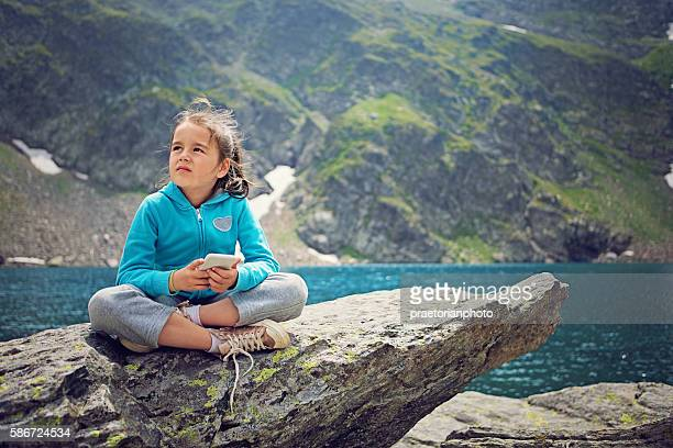 Little girl is resting at the front of mountain lake
