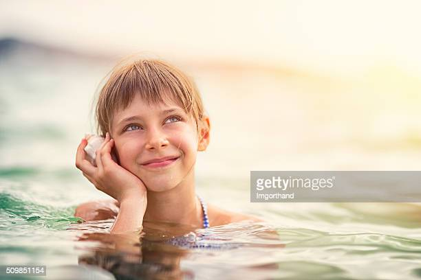 Little girl is sea listening to a sea shell