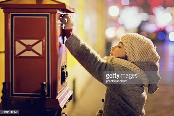 Little girl is sending letter in the night