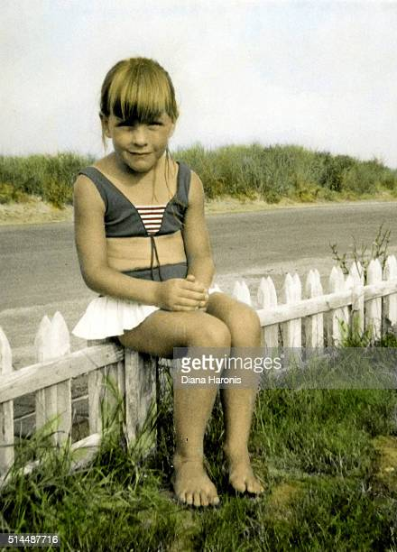 A little girl is sitting on a fence near the beach.