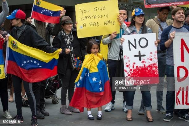 A little girl is wrapped in the Venezuelan flag while activists hold signs during a protest against Goldman Sach's bond purchase transaction of $28...