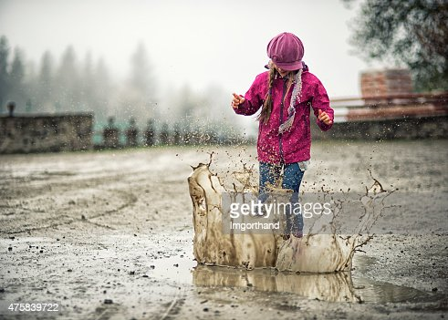 Little girl jumping in moddy puddle