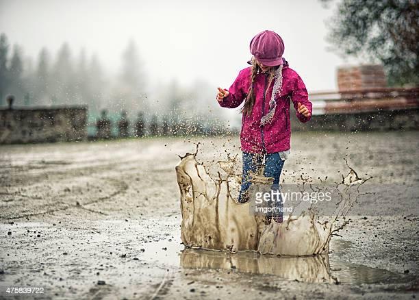 Kleines Mädchen springt in eine Pfütze moddy
