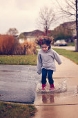 Little girl jumping in rain puddle