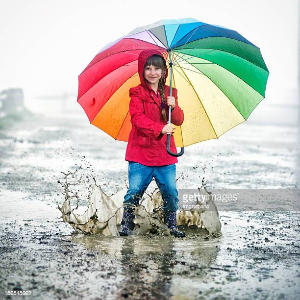 Little girl jumping in the puddles