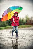 Little girl jumping in the rain