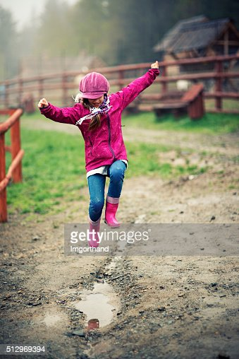 Little girl jumping into spring puddle