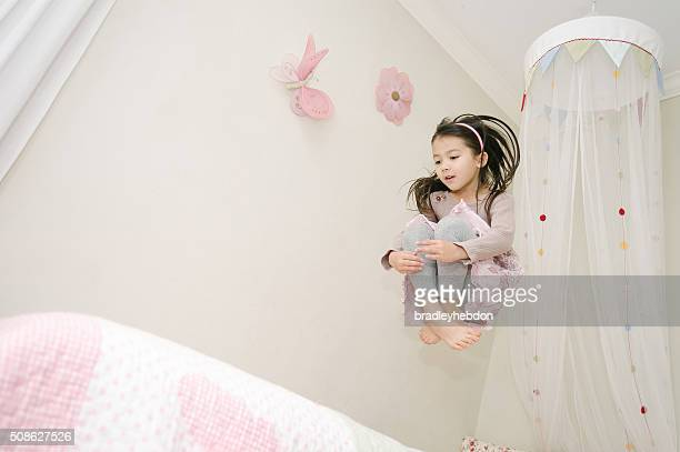 Little girl jumping on her bed