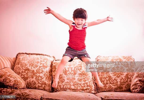 Little girl jumping on the sofa