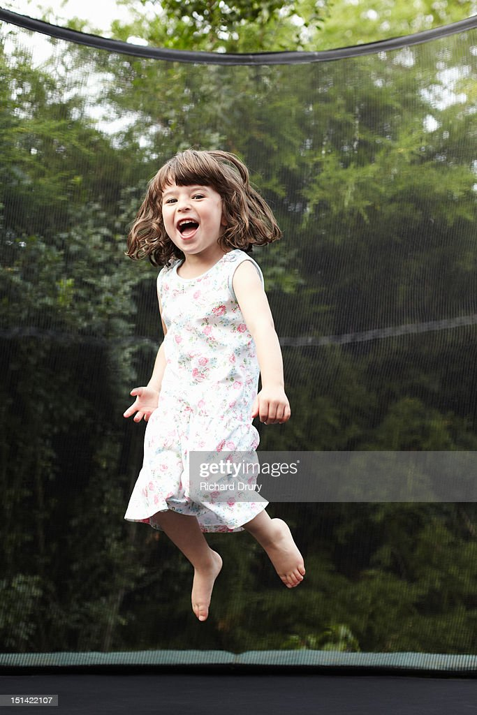 Little girl jumping on trampoline : Stock Photo