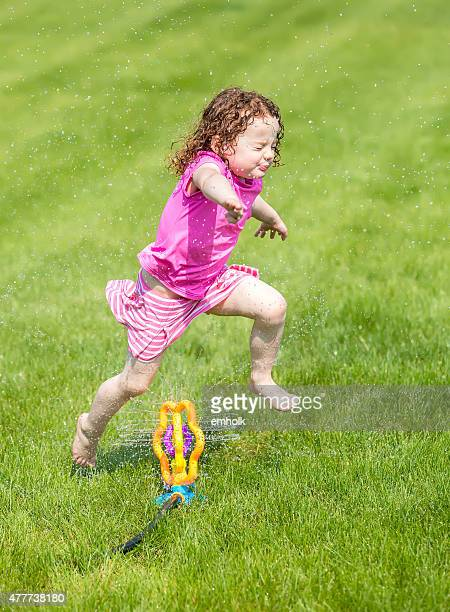 Little Girl Jumping Over Lawn Sprinkler