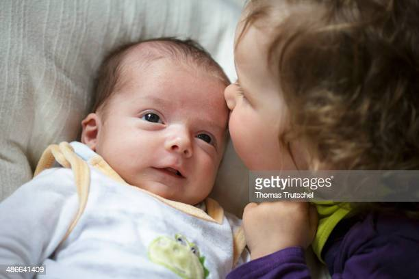 Little girl kissing a 5 week old baby on the head on April 19 in Buecheloh Germany Addition to the family is welcomed