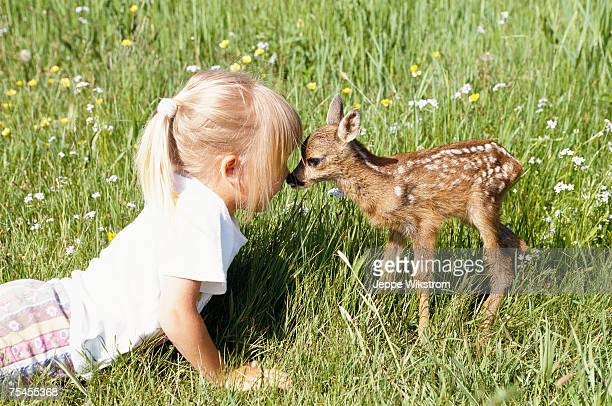A little girl kissing a fawn.
