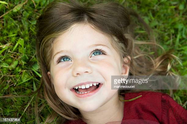 Little girl laughing and lying on grass.