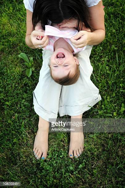 Kleines Mädchen lachen während Mutter kitzelt Ihre
