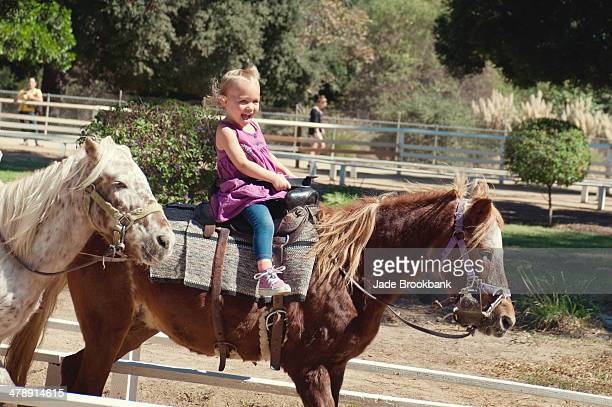 Little girl laughing while riding pony