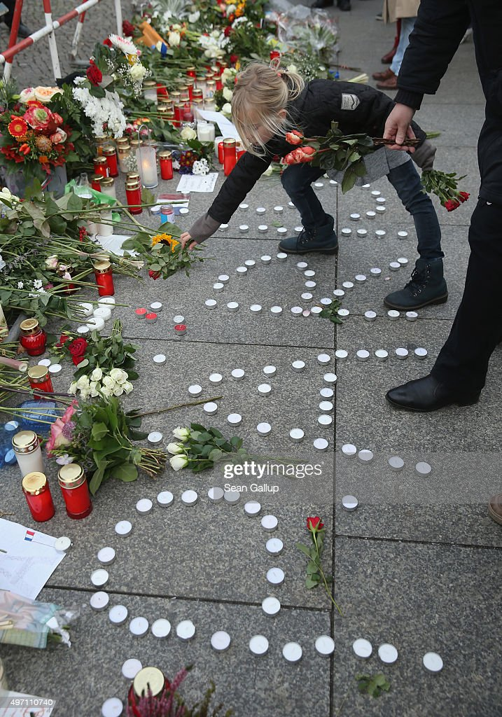 A little girl lays a rose while standing over candlles arranged into the word 'Paris' among flowers and messages left by mourners at the gate of the...