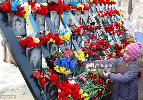 A little girl lays flowers at the memorial where Revolution of Dignity activists or quotHeroes of the Heavenly Hundredquot were killed during...