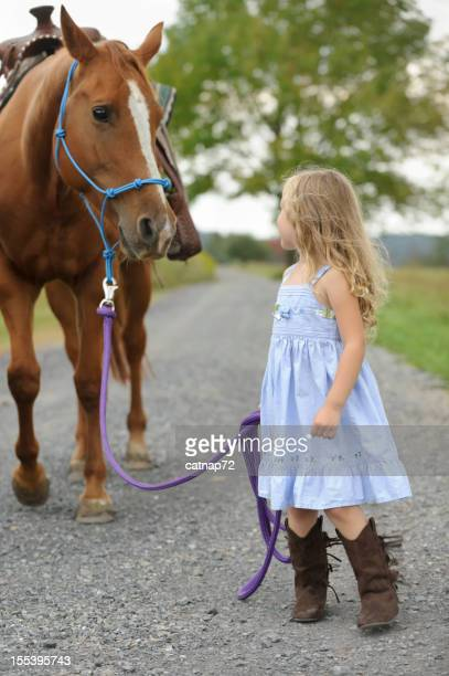 Little Girl Leading Big Horse Down Country Lane