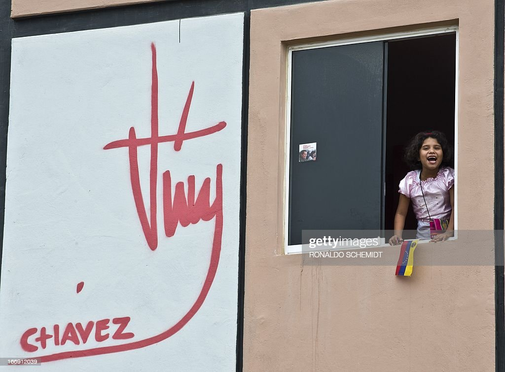 A little girl leans out of a window of her home received from the 'Mision Vivienda', an economic programme of the Venezuelan goverment to provide housing for low-income people, in Ciudad Caribia, Caracas, on April 18, 2013.