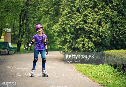 Little girl learning to rollerskate in park