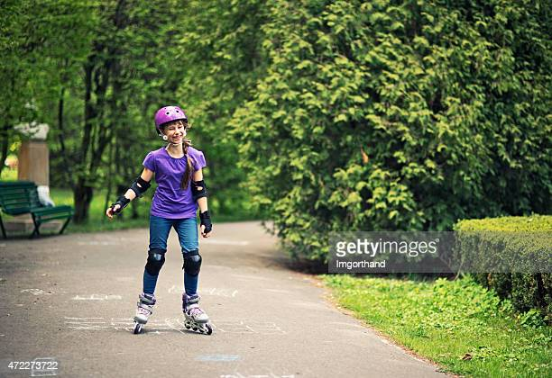 Little girl learning to rollerskate in park